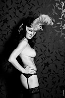 Эротическое фото стоящей у стены девушки в маске с перьями и с обнаженной грудью