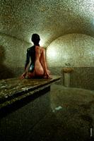 Эротическое фото обнаженной девушки в хамаме со спины, наполовину обмазанной черной глиной