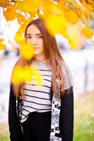 Осенний фотопортрет девушки среди желтых листьев в светлых тонах