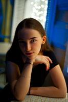 Фотопортрет девушки с рукой у подбородка, сидя за столиком в кафе