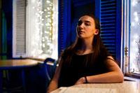 Фото сидящей за столиком в кафе девушки, откинувшись спиной к стене
