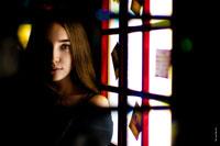Фото девушки в расфокусе рамы и стекол двери телефонной будки