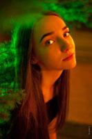 Фото девушки в смешанном цвете: зеленый цвет — от ели, и теплый, красный цвет — от уличных фонарей
