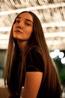 Фотопортрет девушки на фоне расфокусов огней уличной гирлянды