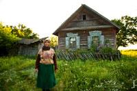 Жанровый фотопортрет сельской женщины в заброшенной деревне на фоне деревянного дома. Белоруссия, Гомельская область, Чечерский район, август 2017