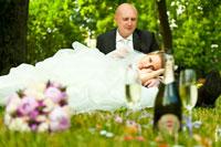 Фотопортрет невесты, лежащей на коленях у жениха, в расфокусах цветов и шампанского