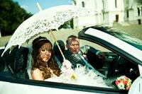Жанровый свадебный фотопортрет невесты и жениха в кабриолете с оригинальным светотеневым рисунком на лицах
