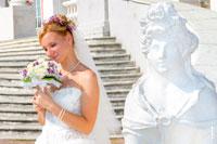 Жанровый фотопортрет невесты с букетом рядом со скульптурой женщины-сфинкса