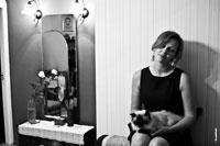 Черно-белое фото девушки с кошкой в квартире и отражение доктора Хауса в зеркале