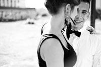 Жанровый ч/б фотопортрет юноши с улыбкой, в объятиях с девушкой