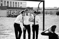 Жанровый фотопортрет 3-х юношей в белых рубашках с галстуками, с футбольным мячом на воротах
