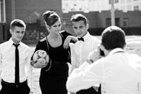 Модный жанровый фотопортрет двух юношей с девушкой, держащей футбольный мяч в руках