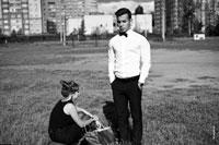 Жанровый фотопортрет юноши в белой рубашке с бабочкой, в застывшей позе, в полный рост, рядом с девушкой
