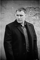 Жанровый черно-белый фото портрет мужчины в пальто, на улице, у стены
