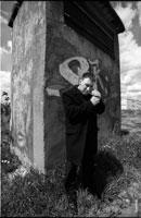 Черно-белый фото портрет мужчины с сигаретой на улице, у стены с граффити