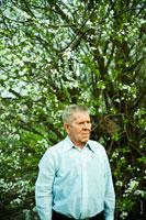Строгий жанровый фото портрет пожилого мужчины на фоне цветущего дерева