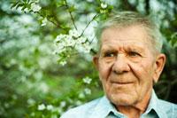 Горизонтальный фото портрет пожилого мужчины с избирательной резкостью на глазах на фоне цветущего дерева