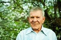 Искренний жанровый фото портрет мужчины весной на фоне цветущего дерева