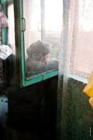 Жанровая фотография пожилого мужчины на балконе, смотрящего в окно
