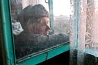 Жанровый портрет пожилого мужчины в шапке-ушанке у окна, фото сквозь грязное стекло