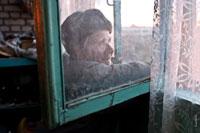 Жанровое фото сквозь грязное стекло пожилого мужчины в шапке-ушанке, смотрящего в окно