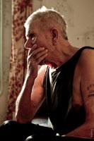 Жанровый мужской фотопортрет старика, закрывающегося рукой