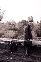 Жанровый портрет мужчины в кожаной куртке, с чемоданом в руке, стоящего у края крыши