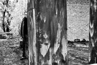 Черно-белое фото мужчины с чемоданом в руке, наполовину спрятавшегося за стеной
