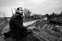 Жанровый портрет мужчины в пальто, сидящего на краю крыши