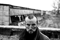 Жанровый портрет строгого мужчины с грязным лицом на фоне развалин