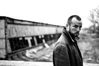 Жанровый ч/б портрет мужчины с грязным лицом на фоне заброшенного здания