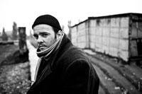 Жанровый черно-белый портрет небритого мужчины в черной шапочке и в пальто с шарфом