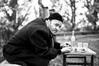 Черно-белый портрет мужчины в черной шапочке и в пальто с шарфом, на улице за столом, с бутылкой и стаканами