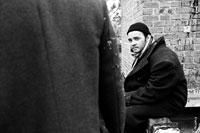 Черно-белый портрет небритого мужчины в черной шапочке и в пальто с шарфом