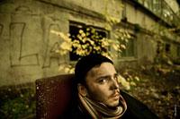Жанровый портрет небритого мужчины в шарфе с грязным лицом, в черной шапочке