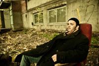 Жанровый портрет мужчины в кресле на улице, в черном пальто и шапочке