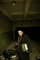 Жанровый портрет мужика в пальто и шапке с электроаппаратами в руках