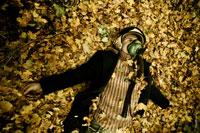 Фотопортрет мужчины в защитном шлеме летчика, лежащего в листве на земле