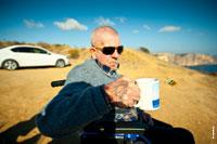 Жанровый фотопортрет мужчины в солнечных очках, с кружкой чая, с татуировкой на руке, на природном фоне
