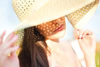Фото женщины в шляпе с солнечными бликами на лице