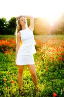 Летнее фото девушки-блондинки в белом платье на фоне макового поля в контровом солнечном свете