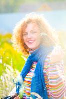 Эмоциональный фотопортрет девушки с улыбкой в ярком цветном свитере в контровом солнечном свете на осеннем пленэре