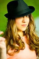 Фотопортрет девушки в черной шляпе с акцентом на взгляде