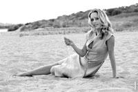 Гламурный фотопортрет девушки в ч/б на песчаном пляже, сидя на песке
