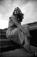 Черно-белый фотопортрет девушки с нижней точки, обхватившей ноги руками