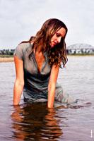 Гламурное фото девушки в мокром платье, сидя в воде