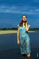 Фото девушки в полный рост, стоящей в воде, на фоне реки и синего неба