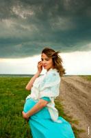 Фотопортрет беременной женщины на природе, на фоне грозового неба