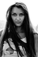 Черно-белый фотопортрет девушки-брюнетки с длинными волосами на пленэре