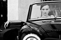 Модный черно-белый женский фотопортрет в старинном кабриолете